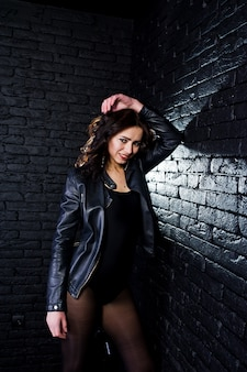 Studio portrait of sexy brunette girl in black leather jacket against brick wall.