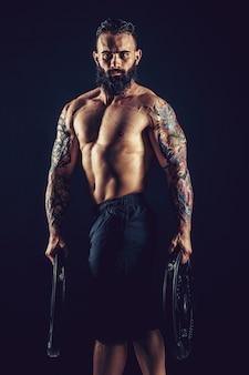 Studio portrait of shirtless tattooed bearded male holds dumbbell