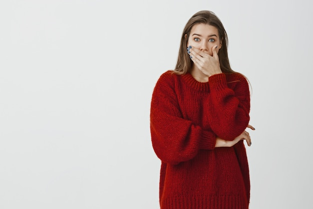 Studio portrait of shocked amazed attractive woman in loose sweater, covering opened mouth with palm and staring terrified , being astonished and surprised