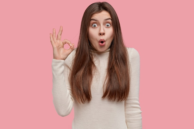 Ritratto in studio di scioccato stupito donna fa il gesto giusto con espressione sorpresa, sorge su sfondo rosa, vestito di bianco ponticello casual
