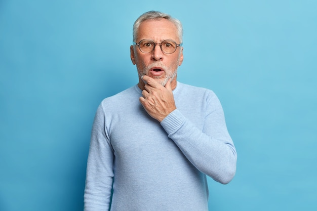 Studio portrait of shocked grey haired senior man holds chin keeps mouth opened hears something astonishing wears long sleeved jumper isolated over blue wall