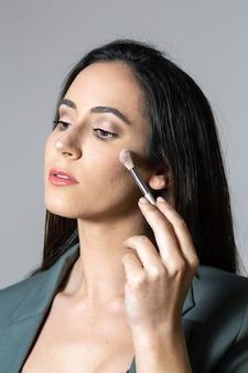 Студийная съемка портрета красивой женщины, позирующей с кистью для макияжа