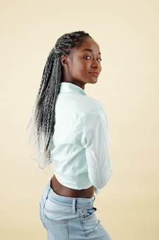 Studio portrait of smiling young black woman with braided hair turning back and looking at camera