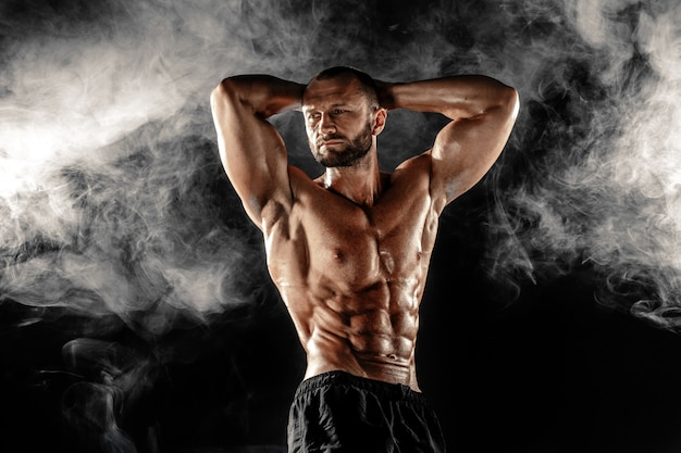 Studio portrait of topless muscular sportsman posing with arms on head over smoke black scene.