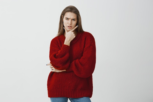 Studio portrait of troubled doubtful attractive woman in stylish red loose sweater, holding gun gesture on chin and frowning, feeling suspicious and frustrated, standing