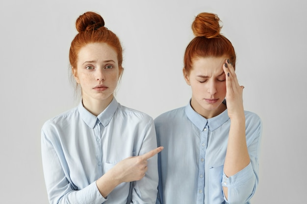 Studio portrait of two redhead sisters looking alike posing indoors