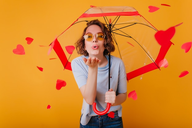 Studio portrait of white girl in sunglasses enjoying valentine's day. indoor photo of amazing woman posing under umbrella with kissing face expression.