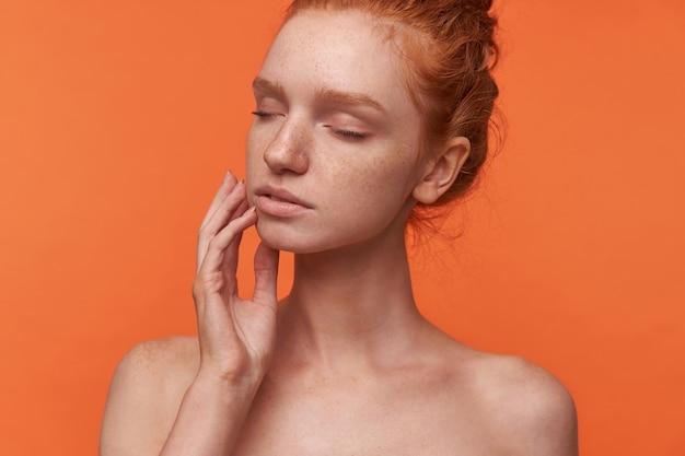 Studio ritratto di giovane attraente readhead donna che indossa i capelli in acconciatura casual in posa su sfondo arancione con gli occhi chiusi, toccando teneramente il suo viso con le dita