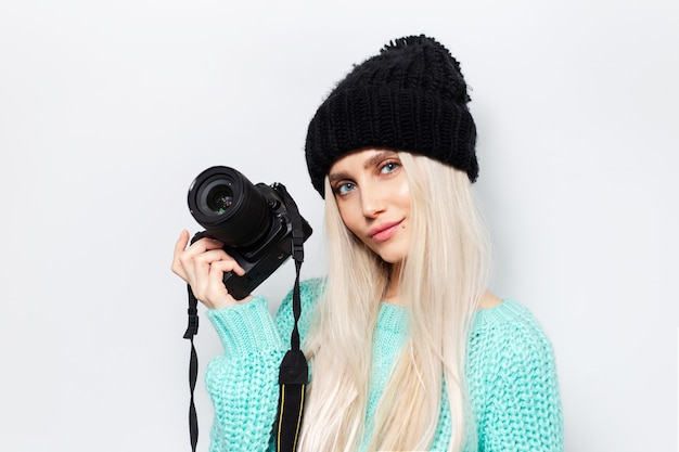 Studio portrait of young blonde girl holding photo camera, wearing blue sweater and black hat on white background.