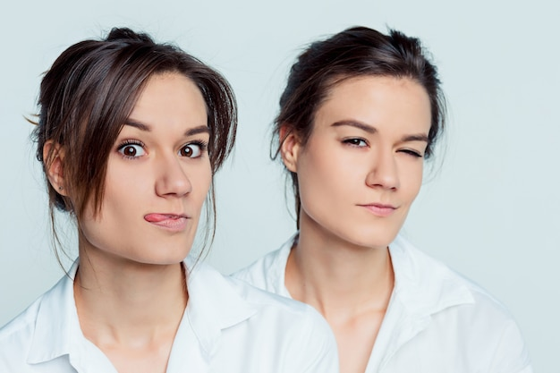Studio portrait of young female twins sisters on gray