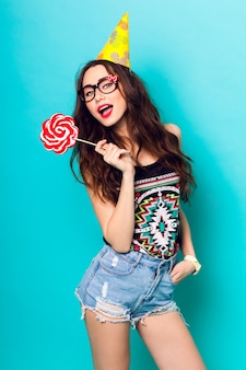 Studio portrait of young funny fashion girl posing on blue wall background in summer style outfit with pink lollipop wearing a paper  hat and cute glasses.