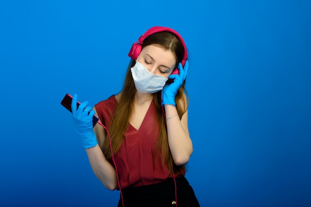 Studio portrait of young girl wearing medical flu mask and disposable gloves, female posing isolated over blue wall. coronavirus, covid19.