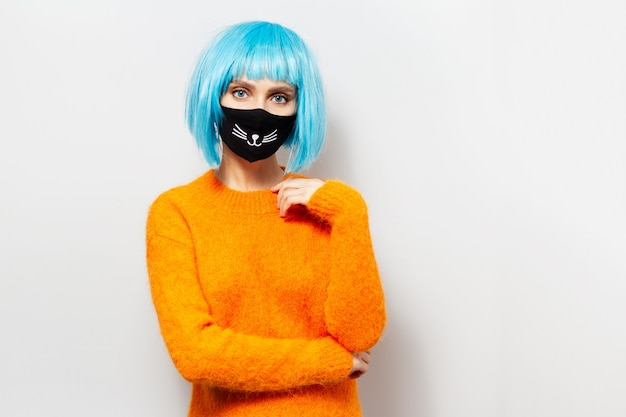 Studio portrait of young girl with blue bob hairstyle, wearing orange sweater and medical mask against coronavirus or covid-19. background of white.