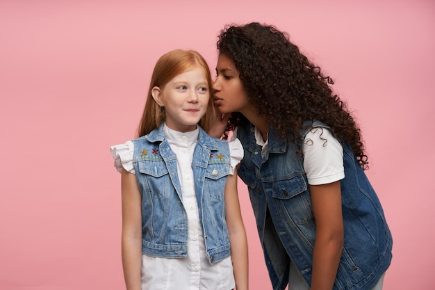 Studio portrait of young lovely long haired girls sharing and telling secret stories by ear, wearing jeans vests and white shirts while standing on pink