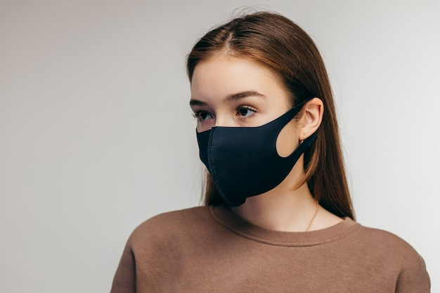 Studio portrait of young woman wearing a black face mask, close up, isolated on gray space