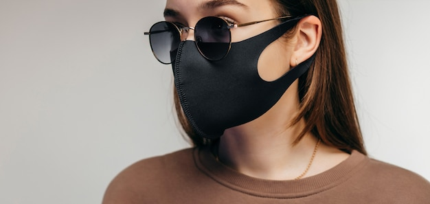 Studio portrait of young woman wearing a black face mask and sunglasses, close up, isolated on gray space