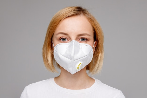 Studio portrait of young woman wearing a face mask, looking at camera, close up, isolated on gray surface. flu epidemic, dust allergy,  protection against virus. city air pollution concept