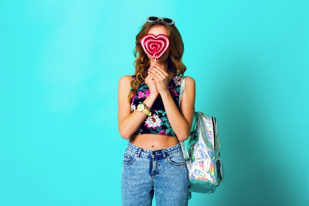 Studio   positive portrait of young sexy funny fashion crazy woman posing on blue wall background in summer style outfit with pink lollipop wearing print  top , neon   backpack  and cute glasses.