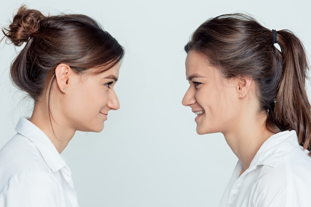 Студийный портрет молодой сестры женского пола на сером