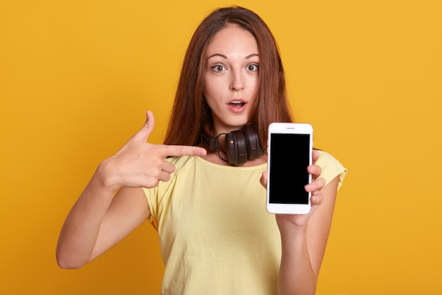 Studio sho of adorable woman showing phone with blank screen and pointing on it with her index finger