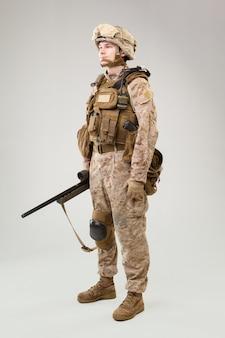 Studio shoot of modern infantry soldier, u.s. marine rifleman in combat uniform, helmet and body armor