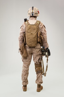 Studio shoot of modern infantry soldier, u.s. marine rifleman in combat uniform, helmet and body armor