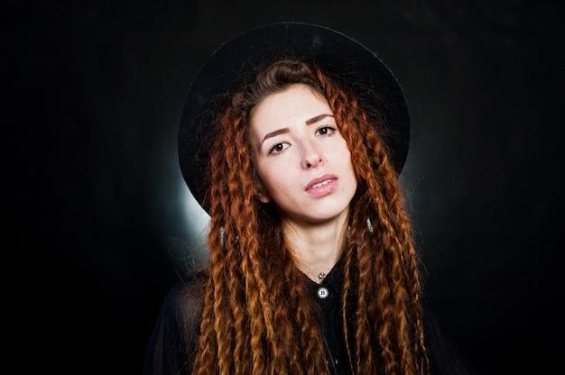 Всход студии девушки в черноте с боязнями и шляпой на черной предпосылке.