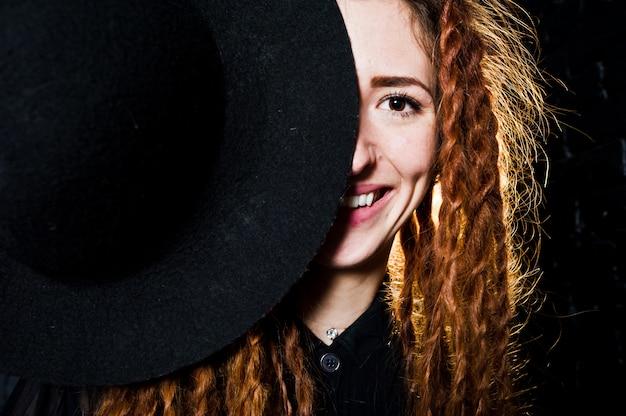 Всход студии девушки в черноте с боязнями и шляпой на предпосылке кирпича.