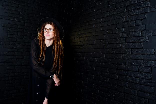 Студия стрелять девушка в черном с боится, в очках и шляпу на фоне кирпича.