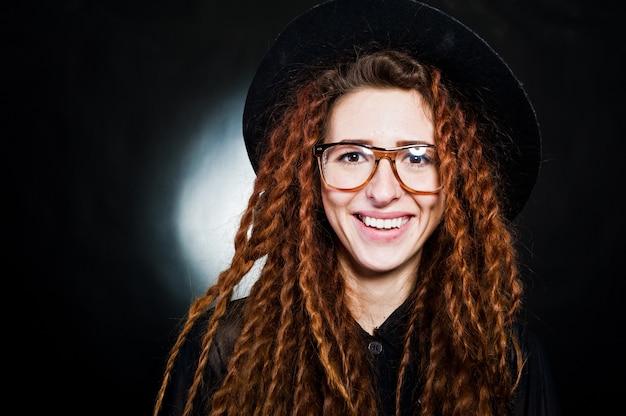 Студия стрелять девушка в черном с боится, шляпа и очки на черном фоне.