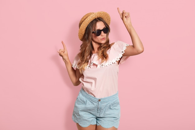 Studio shot of adorable woman with dark hair enjoys of listening to favourite music and dancing, points her index fingers aside, has high spirit, dressed stylish outfit. youth and leisure time concept