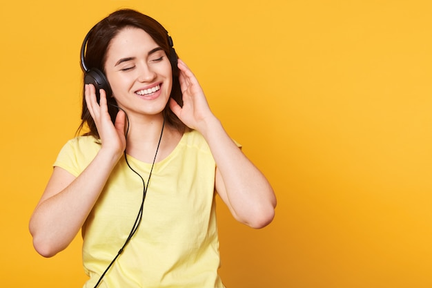 Studio shot of adorable woman with dark hair enjoys of listening to music in headphones
