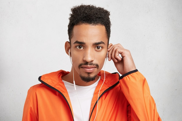 Studio shot of afro american man with stylish hairdo, wears orange trendy anorak, listens to songs in earphones,