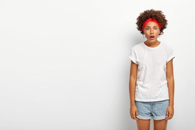 Studio shot di stupito hipster ragazza guarda la telecamera con la bocca aperta