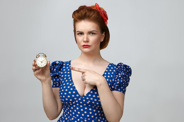Studio shot of angry beautiful young woman dressed in vintage clothes looking at camera with annoyed expression, pointing index finger at alarm clock in her hand, meaning: you are late again