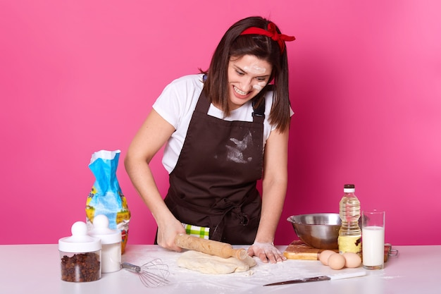 Studio shot of angry housewife dressed kitchen apron dirty with flour, t shirt, red headband, holds rolling out dough, cooking hot cross bun for holiday, looks tired, model posing against studio wall.