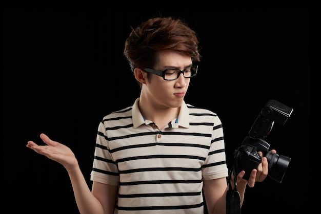Studio shot of asian man against black background looking at camera screen and making helpless gesture with his hands