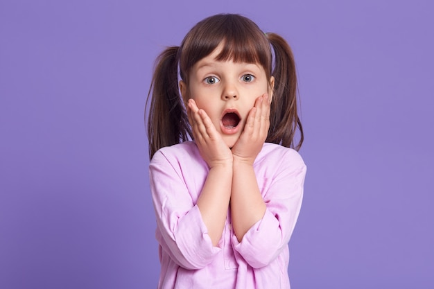 Studio shot of astonished female kid with widely opened mouth