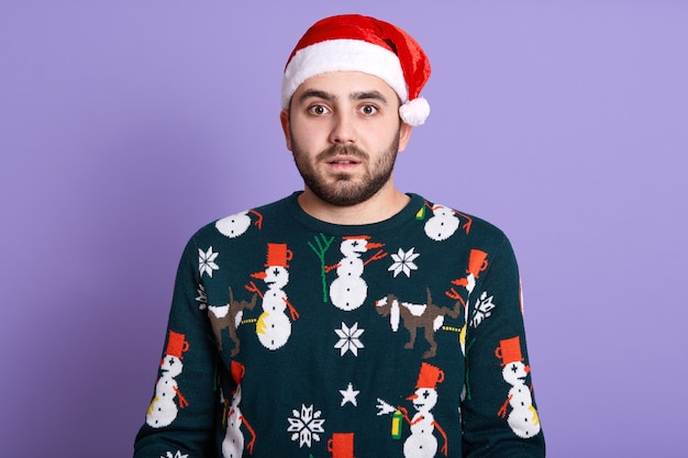 Studio shot of astonished serious man wearing santa hat and funny pullover with snowflakes standing with opened mouth, looking at camera over blue studio