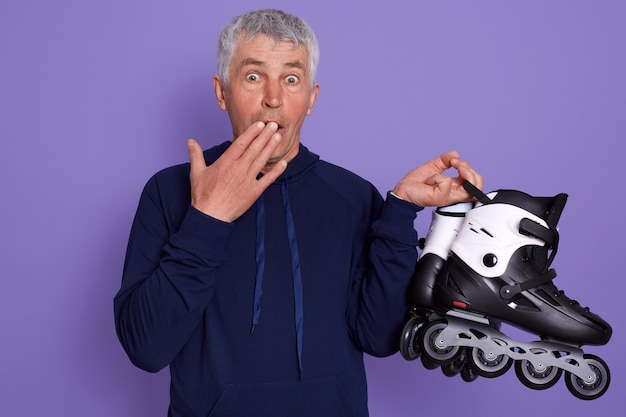 Studio shot of astonished white haired senior man with roller skates in hands