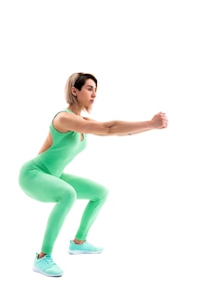 Studio shot of an athletic woman doing squats isolated