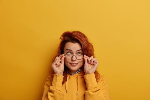Studio shot di attenta bella donna europea guarda seriamente attraverso occhiali rotondi, concentrati sopra