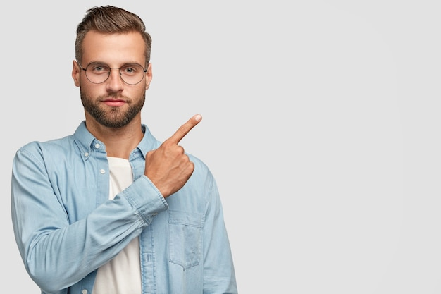 Studio shot of attractive bearded guy posing against the white wall