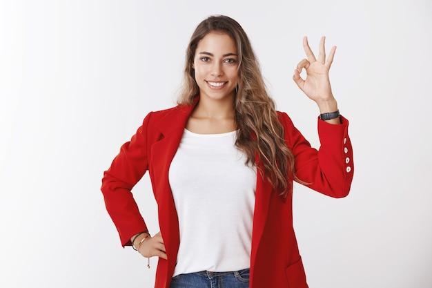 스튜디오에서 촬영한 매력적인 곱슬머리의 25대 여성 리드 팀 관리자는 빨간색 재킷을 입고 만족스러운 제스처 미소, 즐거운 완벽한 팀워크를 보여주는 프로젝트 좋아하는 아이디어를 승인합니다.