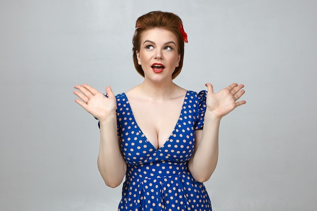 Studio shot of attractive gorgeous young woman wearing stylish retro dress with low cut and red lipstick gesturing emotionally, exclaiming in excitement