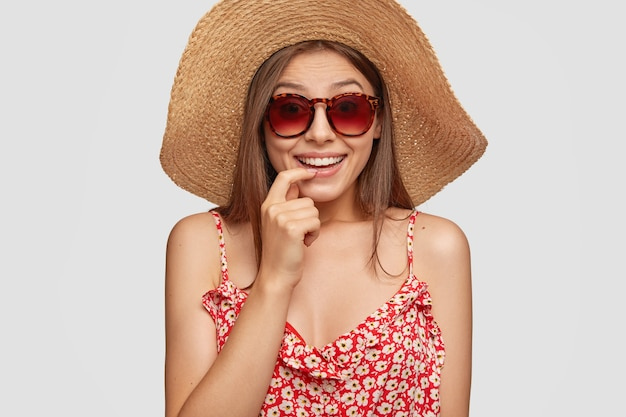 Studio shot of attractive woman has summer vacation, smiles positively and keeps finger near mouth