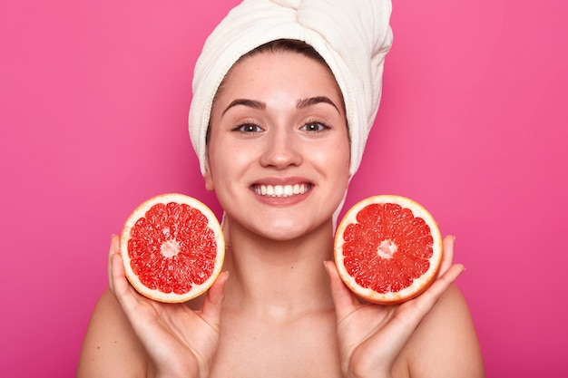 Studio shot of attractive woman with grapefruit in her hands and with white towel on her head, female after taking shower or bath, being in good mood, posing with toothy smile. skin care concept.