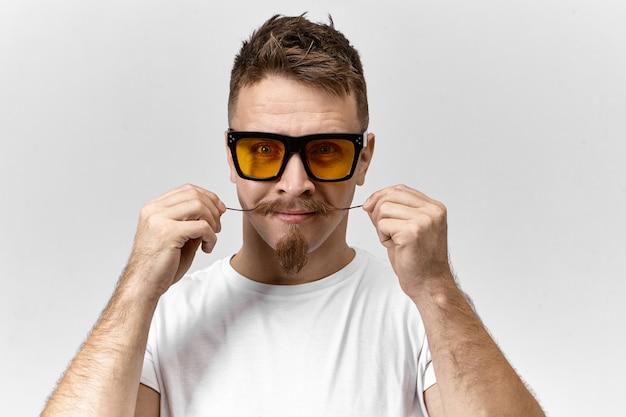 Studio shot di attraente giovane brunetta uomo che indossa eleganti occhiali da sole colorati di giallo e t-shirt casual prendersi cura dei suoi baffi a manubrio, arricciatura termina con la cera, si prepara per la data