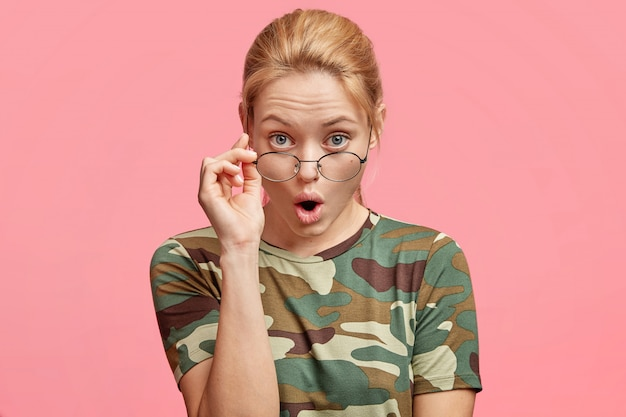 Studio shot of attractive young female model looks through round spectacles with attentive and surprised expression, dressed in casual t shirt, isolated over pink