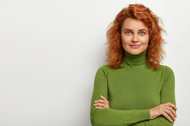 Studio shot of attractive young female model with curly short ginger hair, healthy skin, has gentle smile